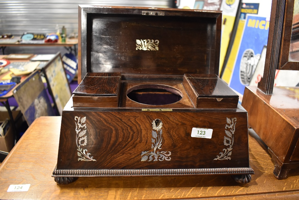 A 19th Century mhogany tea caddy of sarcophagus form with mother of pearl inlay and fitted interior