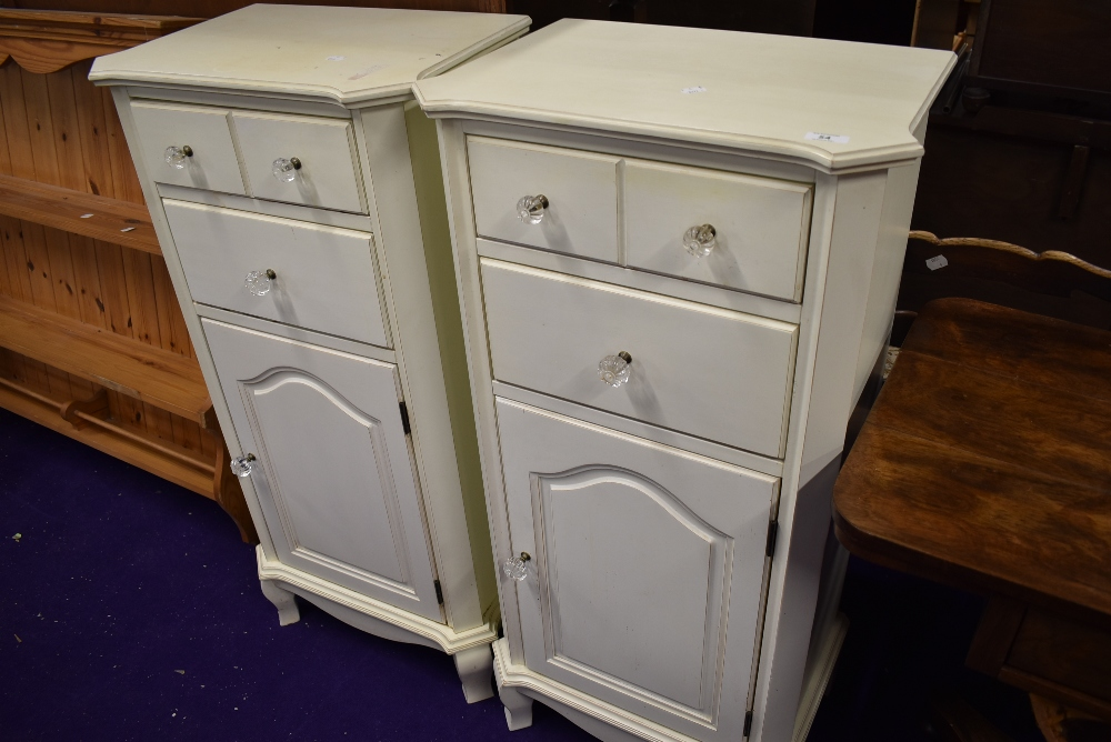 A pair of modern laminate bedside cabinets with drawer and cupboard storage