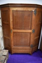 A Victorian oak hall robe, of canted form, in the Arts and Crafts style with cornice detailing,