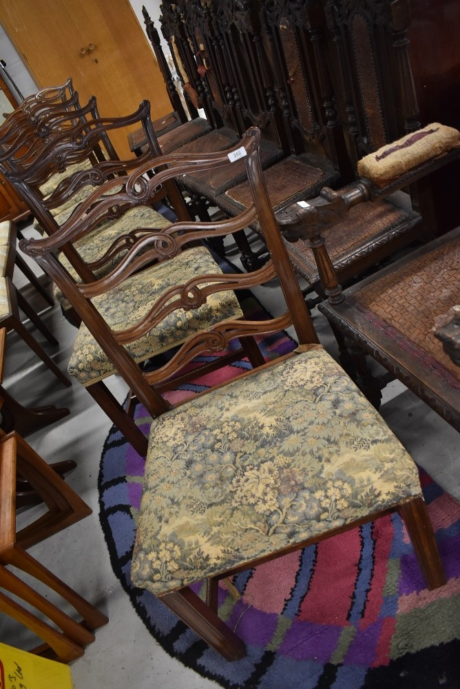 A set of six late 19th or early 20th Century mahogany dining chairs having scroll ladder backs