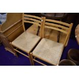 A pair of beech frame rail back kitchen chairs having rush seats