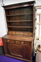A 19th Century oak dresser of naive form, having utility style base on bun feet