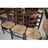 Three 19th Century oak ladder back chairs having rush seats