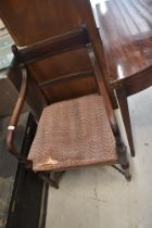 A Victorian carver chair having bow arms on turned frame stretchers
