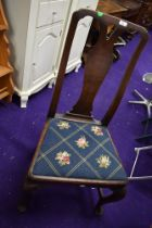 An antique dining chair with mahogany frame on cabriole legs