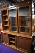 An impressive late Edwardian library book case and cupboard base having oak carcass with sliding