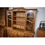 A natural pine kitchen dresser having glazed display top, width approx. 183cm