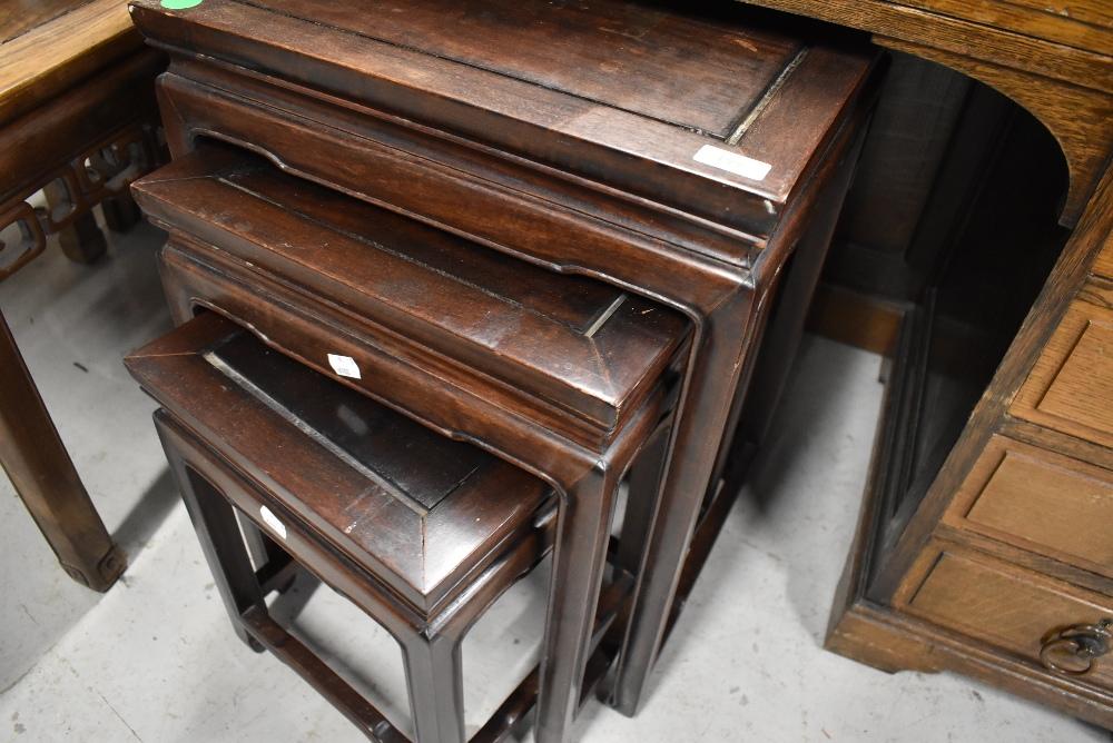 An Oriental hardwood nest of three tables