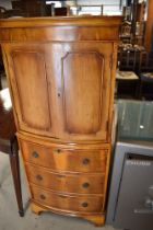 A modern yew wood cocktail cabinet having double cupboard and internal light