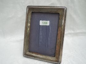 A silver photograph frame of plain rectangular form having a wooden back with easel stand and blue