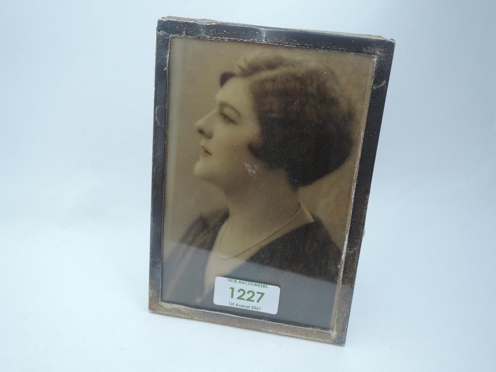 A silver photograph frame of plain rectangular form having wooden easel back, Birmingham 1925,