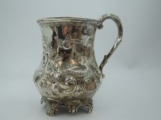 A Victorian silver Christening mug of baluster form having repousse floral, scroll and
