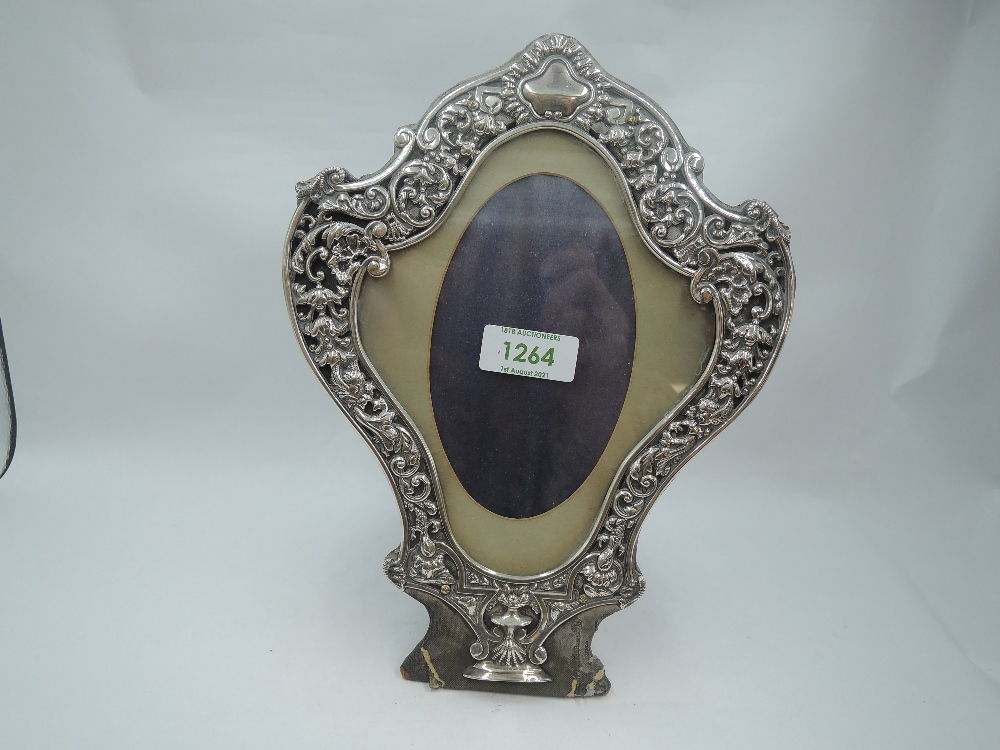 A Victorian silver photograph frame of cartouche form having a silver border with scroll, cherubic