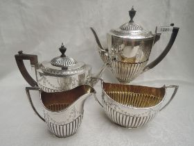 A Victorian silver four piece tea and coffee set having half gadrooned bodies with engraved swag