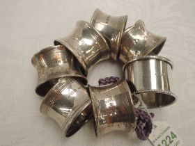 A set of six silver napkin rings of plain form, Birmingham 1945, (1 AF), and a white metal napkin