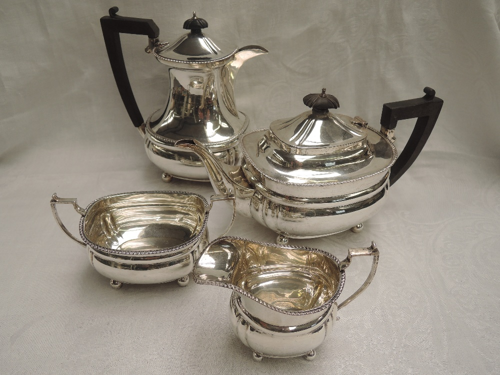 A silver four piece tea set of canted ovoid form having gadrooned rims, wooden handles and knops and