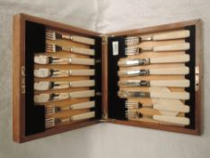 A 1930's cased eight place set of silver fish knives and forks having ivory handles, Sheffield 1937,