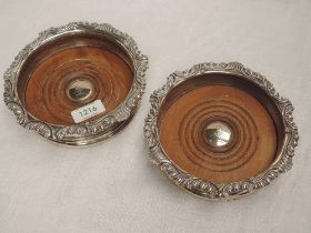A pair of Georgian silver bottle coasters having gadrooned and scroll decoration to rims and