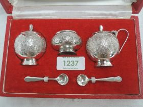 A cased Pakistani silver three piece cruet set of traditional Asian form, retailed by Kashmir Silver