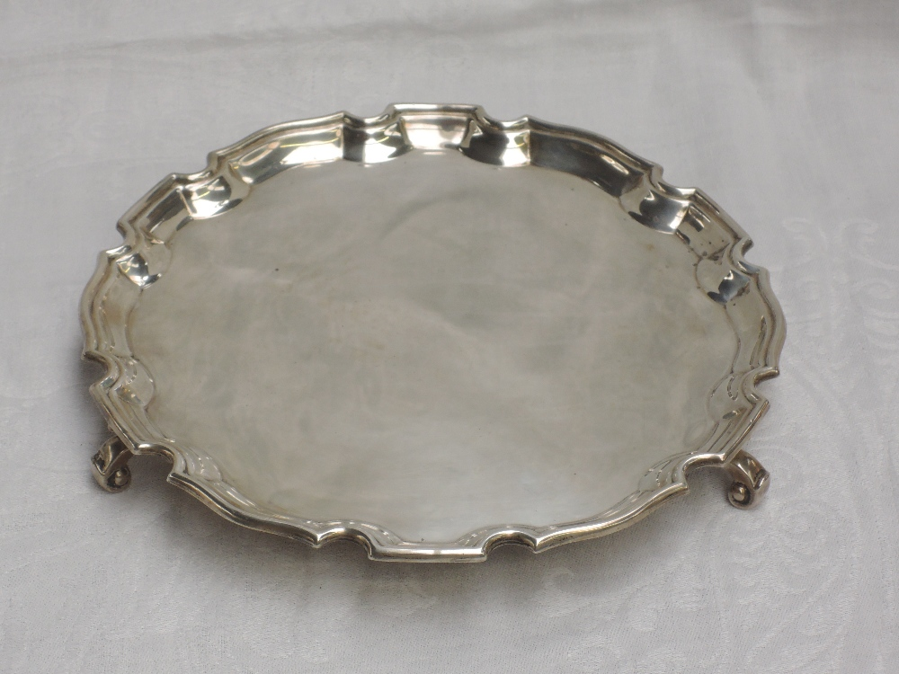 A silver salver of plain circular form having an indented pie crest rim and trefoil scroll feet,