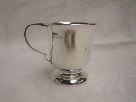A small silver christening mug of plain form on a circular pedestal foot, Birmingham 1966, A T
