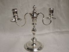 A silver candelabra having central shaped column to three candle holders, two having wax saucers,