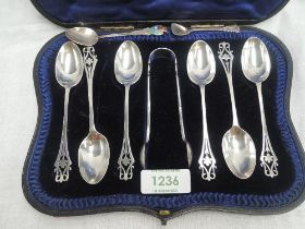 A cased set of six Edwardian silver tea spoons with matching sugar nips having pierced decoration to