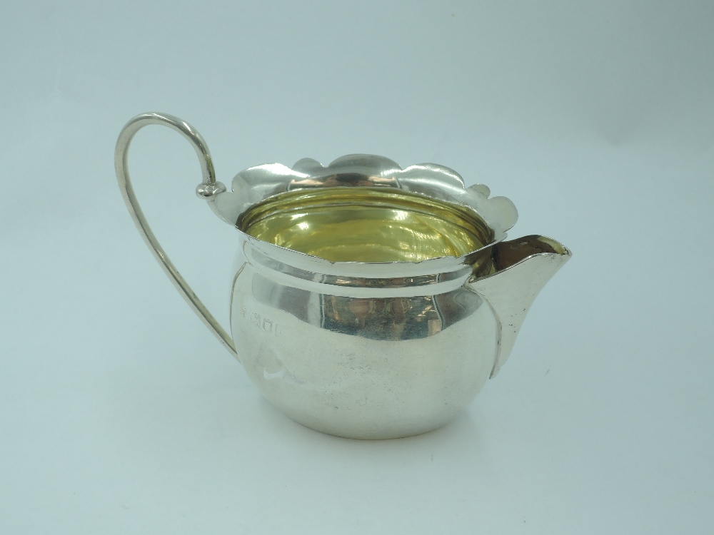 A small Edwardian silver cream jug of oval form having frilled rim, looped wire handle and gilt