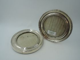 A pair of silver photograph frames of circular form having wooden easel reverse (one stand missing),