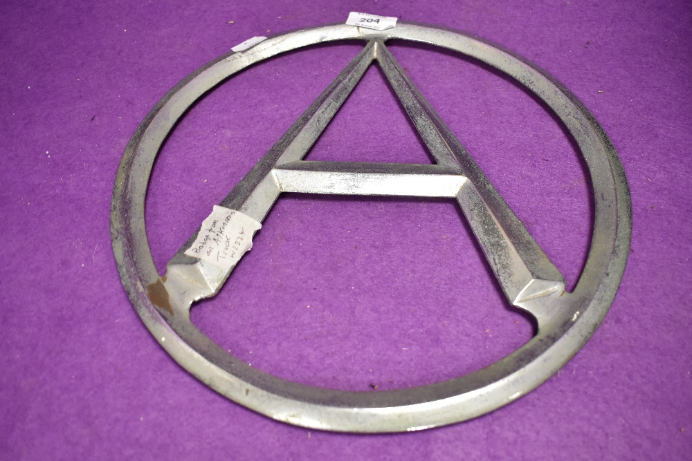 A circular framed letter A in cast metal from an Atkinsons truck