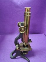 An early 20th century scientific microscope having a brass and cast body with mahogany case made