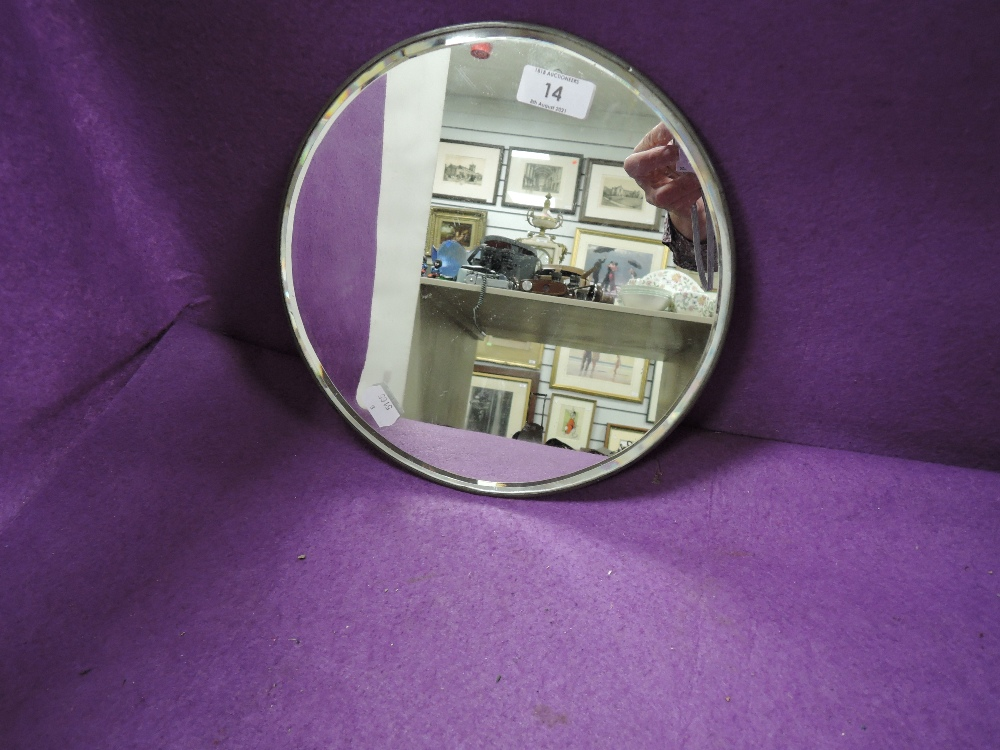 A circular dress or hall way mirror having bevel edged glass and metal frame