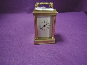 A miniature French brass cased carriage clock having visible escape and bevel edged panels stamped