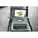 A silver Reed typewriter in case