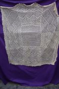 An antique cream christening shawl.