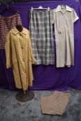 A collection of ladies vintage clothing including rain mac and wool skirt.