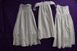 Three Victorian childrens gowns, lace and pin tuck details to hems of some.