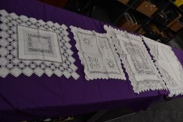 A collection of intricate antique table linen, various techniques used, tray cloths and similar
