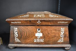 A 19th century rose wood tea caddy of sarcophagus form with mother of pearl inlay and fitted
