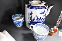 An antique hand decorated porcelain tea pot and two similar tea cups