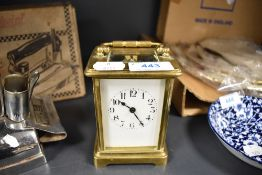 A vintage brass carriage clock having visible escape and enamel face and bevelled glass sides,