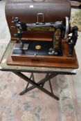 A traditional folding card table and a hand crank sewing machine, American, labelled Wheeler and