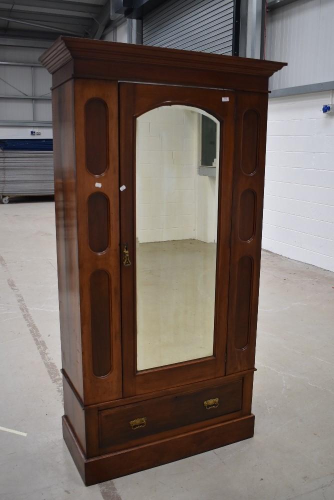 A late 19th or early 20th Century mahogany mirror door single wardrobe