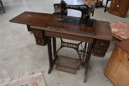 A late 19th or early 20th Century oak cased treadle sewing machine, Singer (serial number) Y7528108