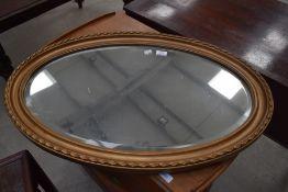 A gilt frame oval wall mirror