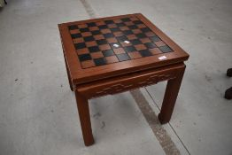 An Oriental hardwood games table, having chess board top and pieces to drawer