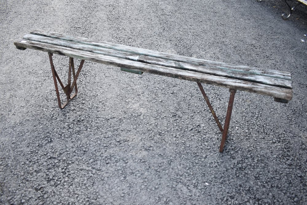 A rustic garden or similar form having metal frame and wooden slat top