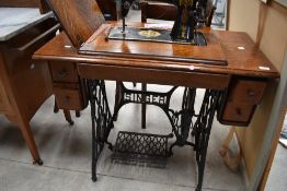 A late 19th or early 20th Century oak case treadle sewing machine, Singer