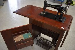 An early 20th Century Singer treadle sewing machine in cabinet, with some accesories