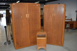 A vintage Austinsuite bedroom suite comprising two graduated wardrobes and a bedside cabinet , in